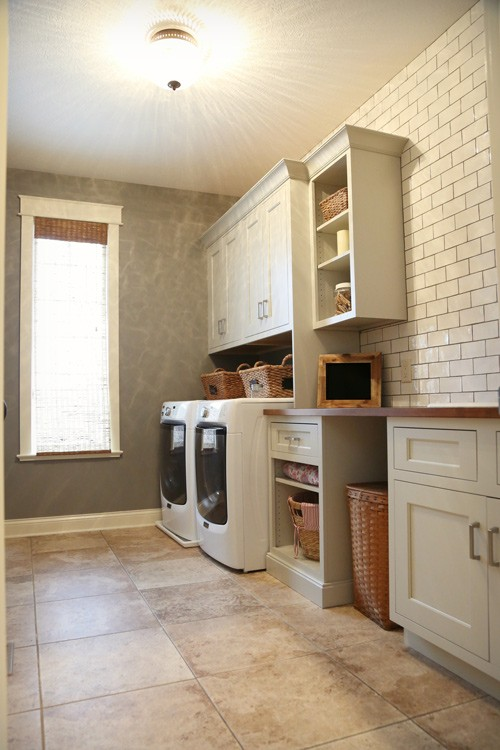 Farmhouse laundry room with subway tile wall