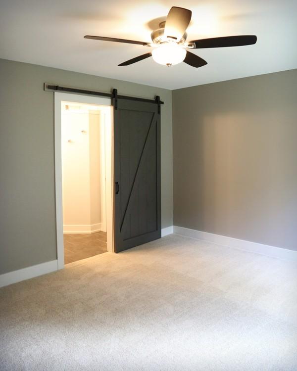 Den with opened sliding barn door entrance